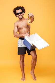 Feliz cara africana em óculos de sol, colocando a garrafa de cerveja em uma geladeira