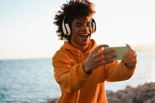 Feliz cara africano da geração do milênio ouvindo playlists de música com aplicativo para smartphone ao ar livre