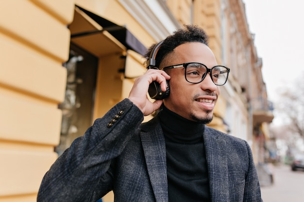 Feliz cara americano ouvindo música durante um passeio pela cidade. jovem africano passando um tempo ao ar livre, curtindo suas músicas favoritas em fones de ouvido.