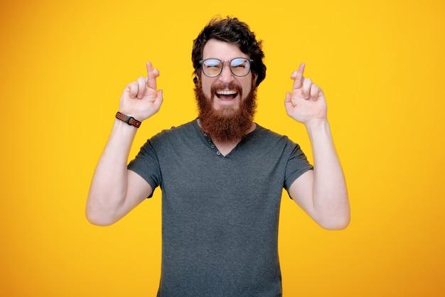 Feliz cara barbudo é ao cruzar o dedo para mais sorte, de pé no amarelo