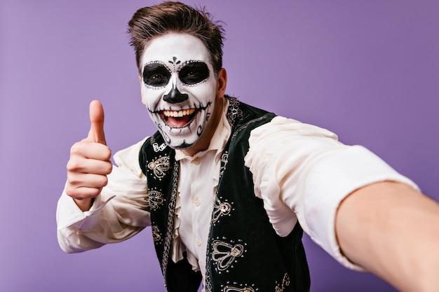 Feliz cara europeu com arte corporal tradicional mexicana, posando na parede roxa. homem estiloso com maquiagem de zumbi, fazendo selfie.