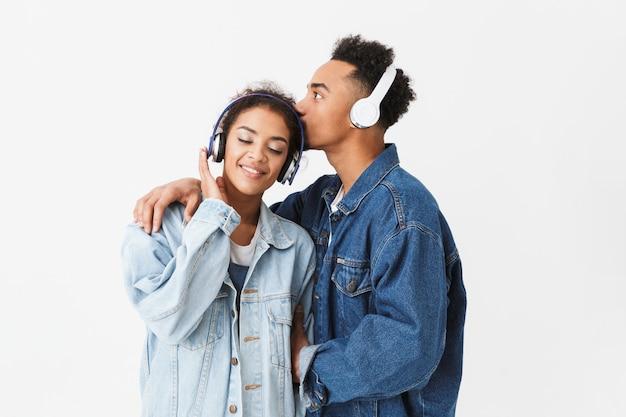 Feliz casal adorável africano em camisas jeans posando juntos e ouvindo música em fones de ouvido enquanto homem beijando sua namorada por cima da parede cinza