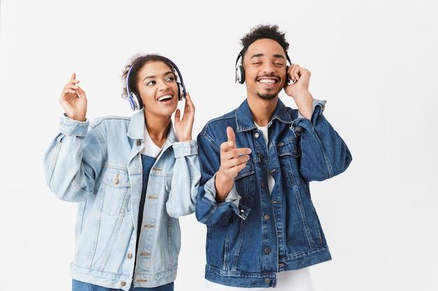 Feliz casal africano em camisas jeans, ouvindo música por fones de ouvido e dançando na parede cinza
