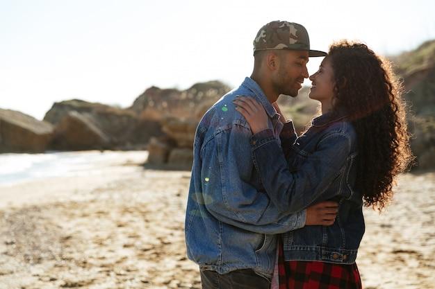 Feliz casal apaixonado africano abraçando ao ar livre na praia
