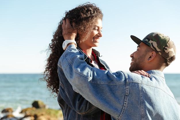 Feliz casal apaixonado africano caminhando ao ar livre na praia