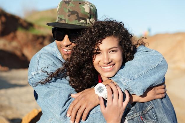 Feliz casal apaixonado africano caminhando ao ar livre na praia.