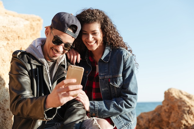 Feliz casal apaixonado caminhando ao ar livre na praia conversando por telefone.