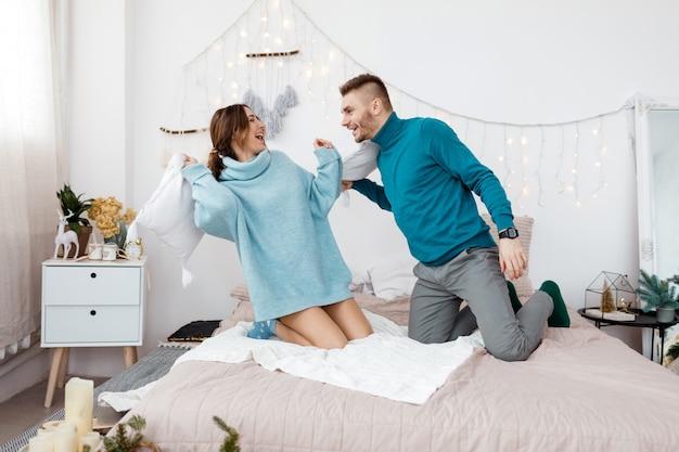 Feliz casal apaixonado elegante tendo uma luta de almofadas na cama, jovem e mulher esperando bebê para o natal, foco seletivo