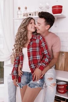 Feliz casal apaixonado estão abraçando e se divertindo na cozinha no dia dos namorados de manhã. elegante homem e mulher com cabelos longos, relaxando em casa