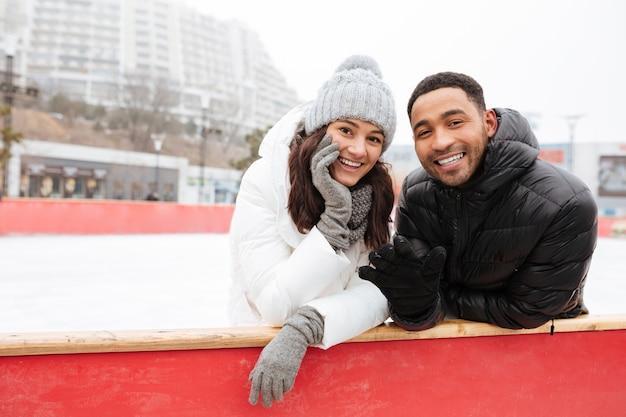 Feliz casal apaixonado patinando na pista de gelo ao ar livre.