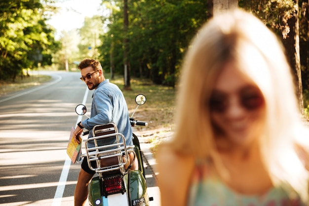 Feliz casal apaixonado perto de scooter ao ar livre. olhando de lado