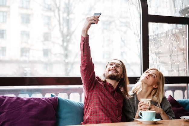 Feliz casal apaixonado sentado no café e fazer um selfie.
