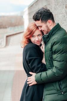 Feliz casal apaixonado, sorrindo e se abraçando na rua. história de amor de duas pessoas felizes - retrato em plano médio