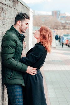 Feliz casal apaixonado, sorrindo e se abraçando na rua. história de amor de duas pessoas felizes - retrato plano médio