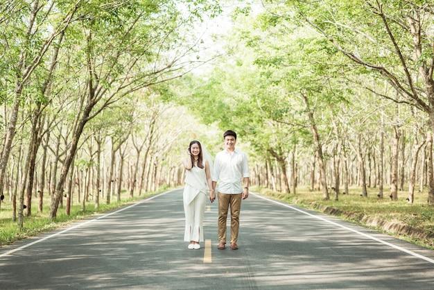 Feliz casal asiático apaixonado na estrada com arco de árvore