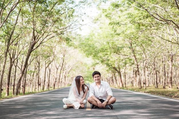 Feliz casal asiático apaixonado na estrada com um arco de árvore
