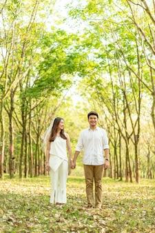 Feliz casal asiático apaixonado por arco de árvore