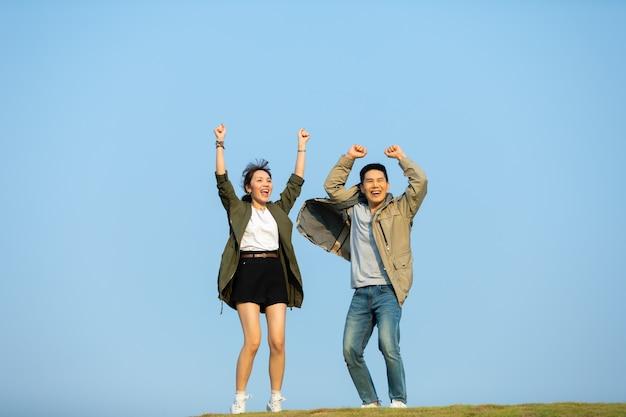 Feliz casal asiático, caminhadas alegres de mãos dadas na zona rural.