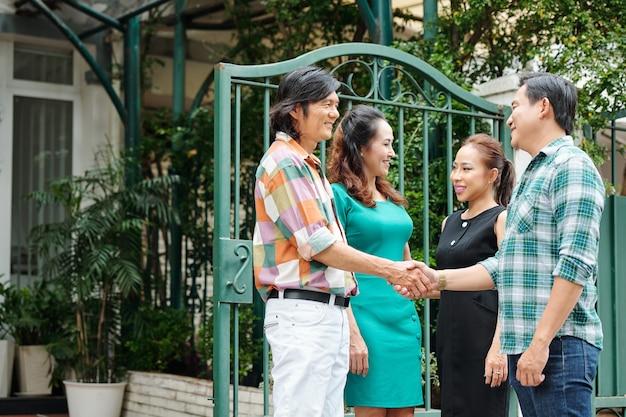 Feliz casal asiático de meia-idade cumprimentando amigos nos portões de sua casa