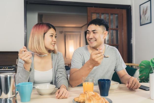 Feliz casal asiático doce tomando café da manhã, cereais no leite, pão e beber suco de laranja