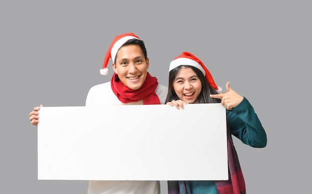 Feliz casal asiático em pano de tema de natal, apresentando faixa em branco para publicidade