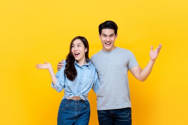 Feliz casal asiático jovem abraçados sorrindo e abrindo as mãos