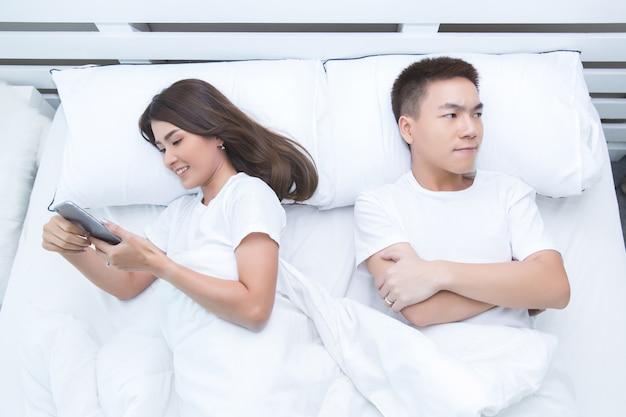 Feliz casal asiático na cama em casa