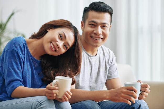 Feliz casal asiático sentado no sofá em casa com canecas de chá e sorrindo