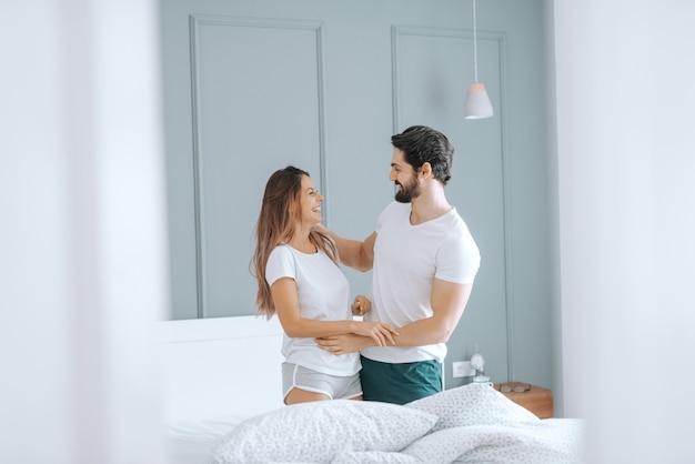 Feliz casal caucasiano de pijama, sorrindo e se abraçando na cama pela manhã. interior do quarto.