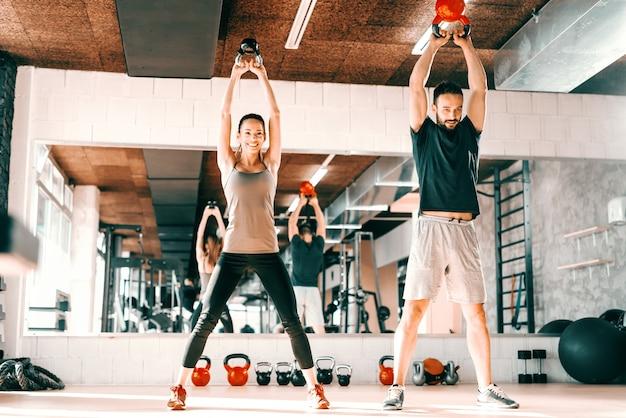 Feliz casal caucasiano fazendo exercícios de força com kettlebell em pé no ginásio. no espelho de fundo com seu reflexo.