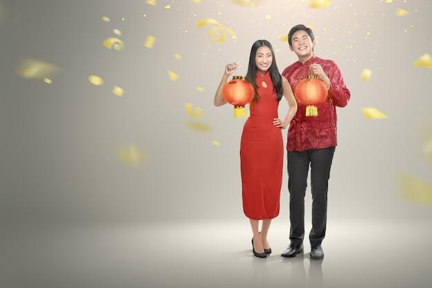 Feliz casal chinês em roupas cheongsam segurando lanternas vermelhas