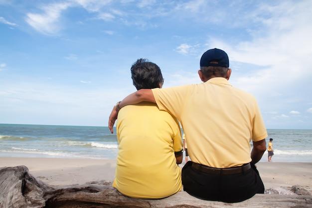 Feliz casal de idosos asiáticos sentado e olhando para a praia, vista traseira