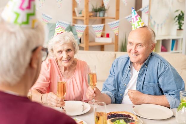 Feliz casal de idosos com chapéu de aniversário brindando com champanhe na mesa servida