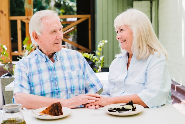 Feliz casal de idosos comendo bolo