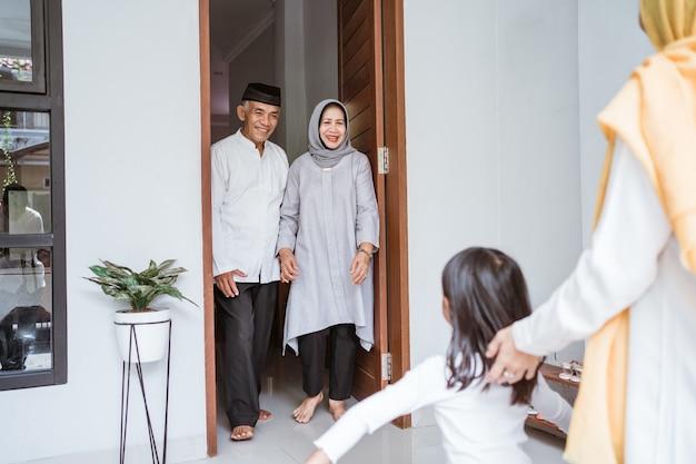 Feliz casal de idosos muçulmanos asiáticos conhecendo filhos e netos na porta da casa durante a celebração do eid mubarak