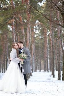 Feliz casal de noivos ao ar livre no dia de inverno