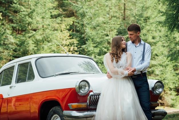 Feliz casal de noivos de luxo se beijando e se abraçando perto de um carro retrô