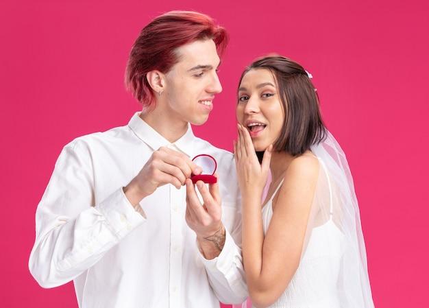 Feliz casal de noivos, do noivo e da noiva, fazendo propostas com um anel de casamento em uma caixa de presente, felizes e animados em pé sobre a parede rosa