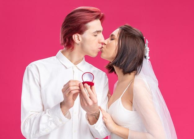 Feliz casal de noivos fazendo casamento com um anel de casamento em uma caixa de presente, felizes e apaixonados, beijando-se em pé sobre a parede rosa