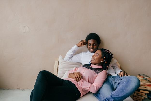 Feliz casal de pele escura relaxante dentro de casa.