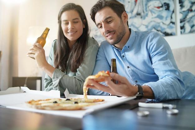 Feliz casal descontraído compartilhando uma pizza em casa