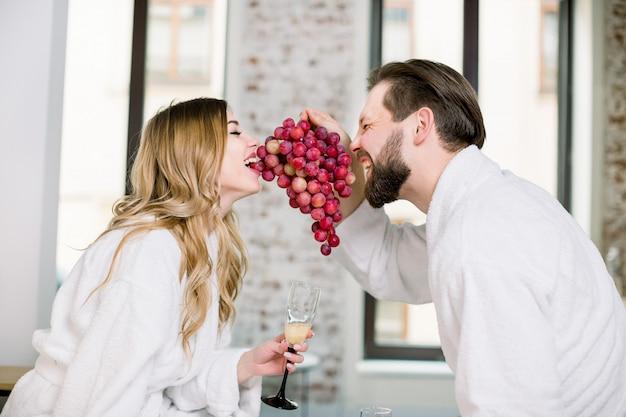 Feliz casal engraçado em roupões de banho comendo frutas frescas, mordendo uvas juntos, sentado na cama no quarto de hotel