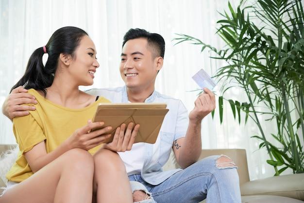 Feliz casal étnico com tablet e cartão de crédito