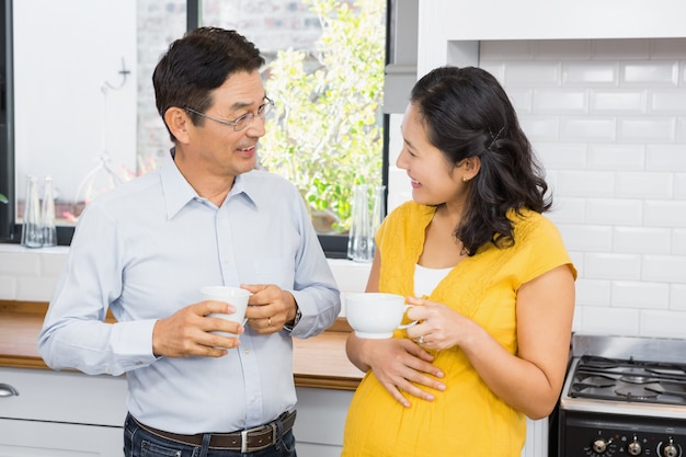 Feliz casal expectante conversando na cozinha