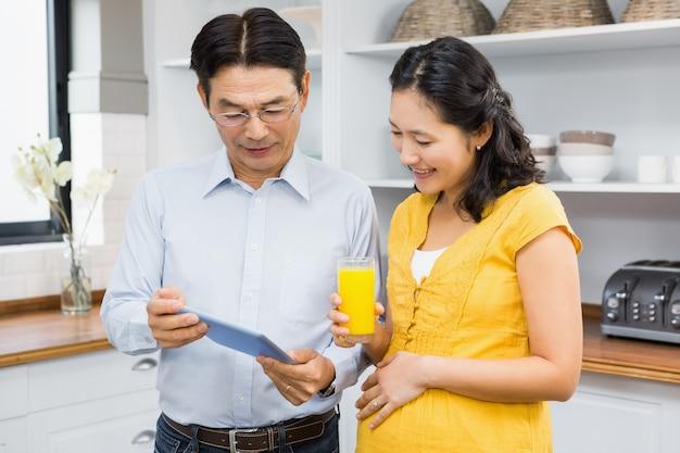 Feliz casal expectante usando tablet na cozinha