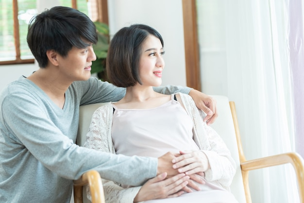 Feliz casal grávida animado se divertindo em casa. alegre mãe expectante e pai sentado no sofá, olhar pela janela, sorrindo, rindo. apreciando o conceito de gravidez