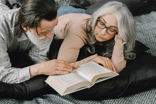 Feliz casal idoso relaxando juntos em casa. casal sênior lendo livro na cama.