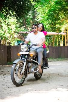Feliz casal indiano asiático andando de moto ou moto em estradas florestais
