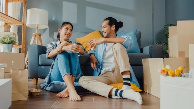 Feliz casal jovem asiático, homem e mulher, sentam-se na nova casa, bebem café e conversam com o armazenamento da caixa de embalagem de papelão