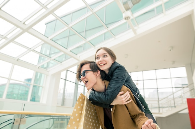 Feliz casal jovem bonito segurando sacolas de compras em pé no shopping.